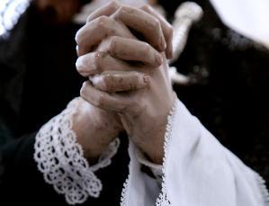 MANI GIUNTE IN PREGHIERA A SIMBOLEGGIARE LA GRANDE ATMOSFERA DI UNA FESTA RELIGIOSA PUGLIESE. MANI DI UNA STATUA CHE ATTRAVERSA I VICOLI INSIEME AD ALTRE 20 STATUE.