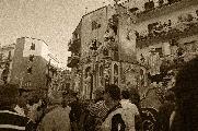 Tutta la gente per le strade e dai balconi assiste il maestoso carro trionfale, fatto di umile carta e che porterà la Madonna in processione.