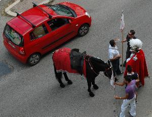 """Il cavaliere a terra non soccorre alla stanchezza del cavallo di razza. Passa """"distrattamente"""" un'autovettura di razza, carica come un mulo da soma."""
