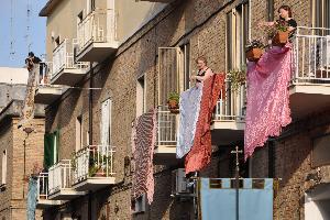 Foto di Francesco Morelli. Alcuni fedeli di via Cappelluti omaggiano la Madonna esponendo i copriletti più belli.