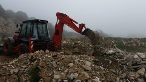 Escavatore dei Vigili del Fuoco esegue scavi per monitare strati profondi dei rifiuti
